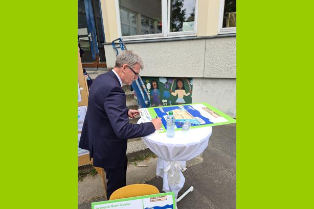 Der Bezirksbürgermeister Helmut Kleebank signiert das Plakat