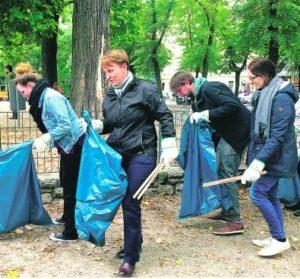 Vier Menschen machen zusammen den Park sauber