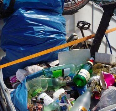Müllsack und Flaschen in einem Boot